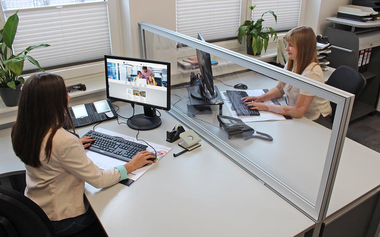 Schreibtischtopper light auf einem Schreibtisch zwischen zwei gegenüberliegenden Arbeitsplätzen