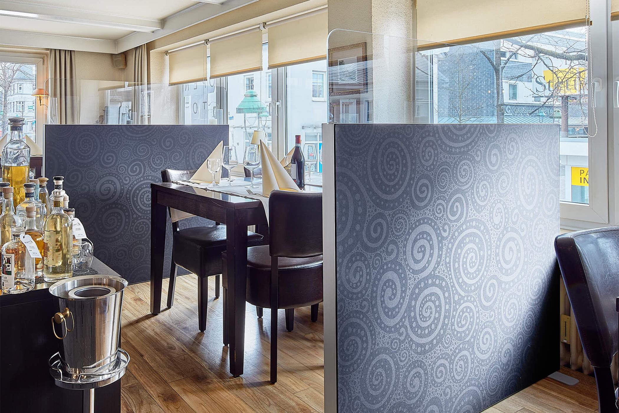 Trennwand Basic mit Acryltopper  mit einem schwarzen Muster bedruckt steht in einem Restaurant als Trennelement zwischen zwei Tischen.